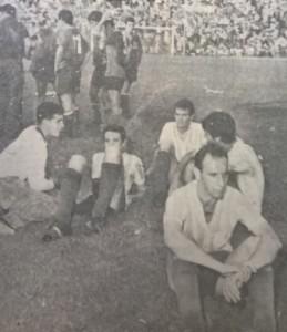 Los jugadores de Racing sentados, a la espera que los hinchas abandonen el campo de juego. Fueron veinte minutos que le quitaron el ritmo al equipo.